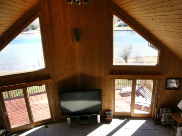 Living room, with a view of the river and a 73-inch television.