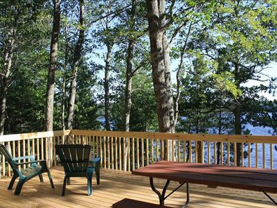 The large new deck features Adirondack chairs, a picnic table, and grill
