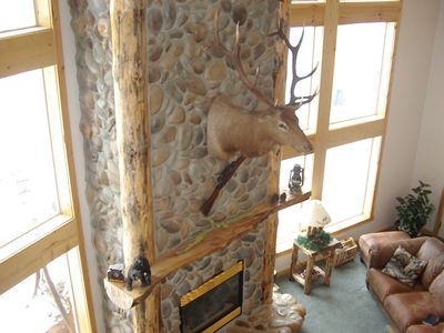 elk mounted on rock fireplace as seen from loft