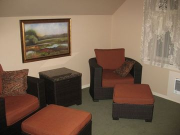 Upstairs living room has a two roomy chairs, leather sectional, TV, & DVD player