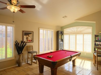 Game room with pool table and electronic dart board in the corner.