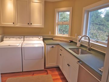 The laundry room is just off the kitchen and has a sink and the extra dishwasher