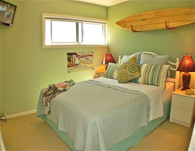 The blue-green surfing bedroom echos the color of the ocean