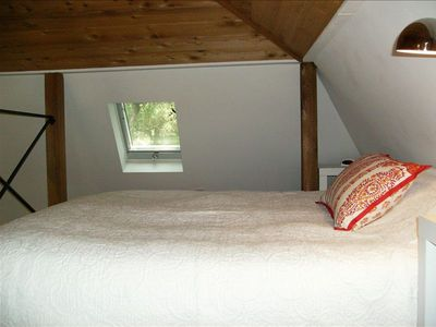 Loft sleeping quarters with queen bed and operable skylight.