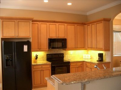 Fully equipped kitchen with granite countertops, abundant cabinet & pantry space