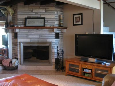 "Living room with wood fireplace and 46"" television & DVD player."