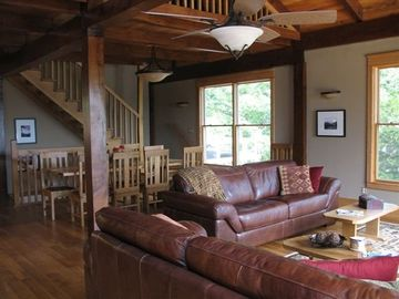Lake Ozark house rental - Great room couch/dining area. Note the view of trees thru oversized windows.