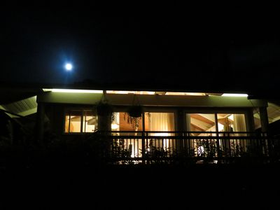 Full moon over cottage. Architectural soffit lightning creates a warm glow.