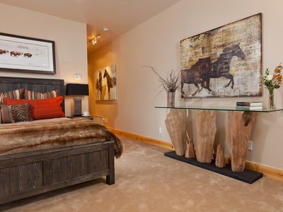 master suite designer console, plush carpeting, contemporary western paintings