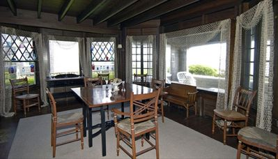 Fishnet curtains grace the windows and painted dining room furniture add charm.