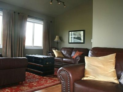 The living room has wood floors, comfortable seating and antique furnishings.