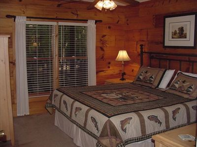 Main level bedroom has king size bed, iron headboard and rustic pine furniture