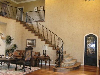 Curving wrought-iron staircase leads guests upstairs to bedrooms and media room.