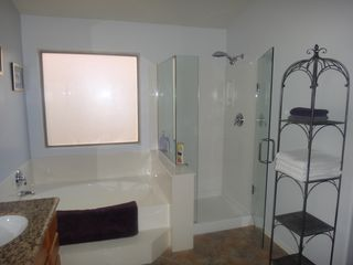 Goodyear bungalow photo - Reglazed shower with frameless glass surround. Granite vanity/dual sinks.