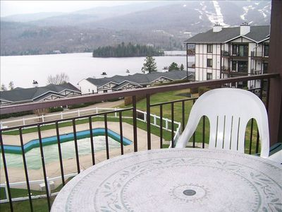Balcony. Patio furniture includes table chairs and lounger. Ski hill is visible.