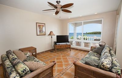 Ocean view living area with flat screen tv and two large couches
