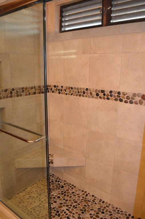 Tile shower with new glass doors and pebble accents and floor