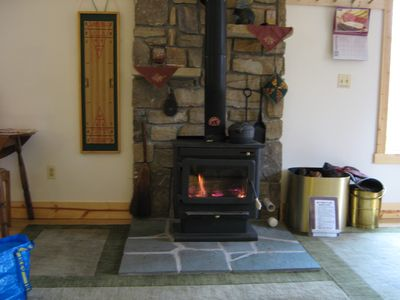 View the fire in the wood stove from the couch. Wood in rick on porch in season.