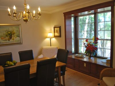 Spacious formal Dining Room with leather chairs and window seat overlooking pool