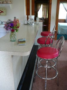 the cottage has old fashioned at-the-counter seating and a kitchen table