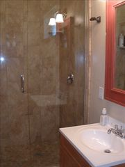 Paso Robles barn photo - Limestone bathroom with extra large walk in shower and natural rock floor
