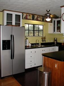 The kitchen has full-sized appliances, including a large refrigerator/freezer