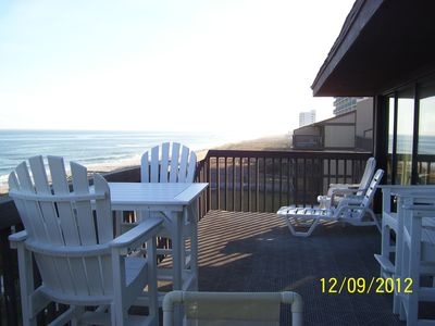 Large private deck with high rise table for dining and sunning at Sea Colony
