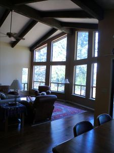 This is the living room with high ceilings and a  view out towards the mountains