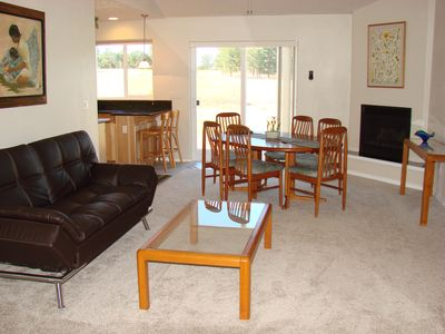 Living area looking out onto large deck, corner fireplace, big screen TV