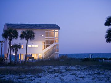 House at dusk. Covered Parking. Very private beach
