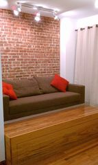 Queens studio photo - Sofa Turns into Long Twin Bed. Queen Tempur-Pedic Bed Rolls Out from Platform.