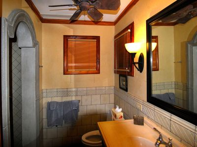 The guest bath has the same teak, stonework, and arches as the master bath.