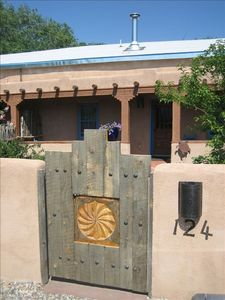 Handcrafted gate entry to 1796 adobe, with Historic La Loma Plaza symbol