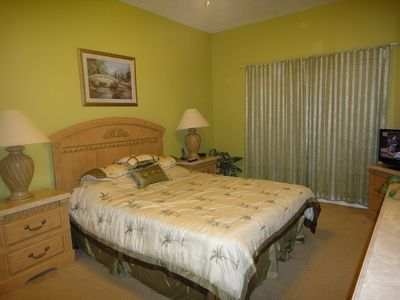 2nd downstairs master suite bedroom with queen sized bed and flat TV