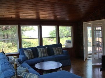 Sunroom surrounded by windows w/ water view, a 47' Plasma, couches & dining tabl