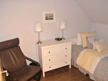 A smaller bedroom 3 with twin bed and 3 drawer dresser.