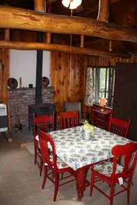 Living/dining area with log beams, woodstove, seating, access to the front porch