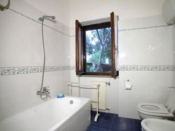 Bathroom with tub and overhead shower