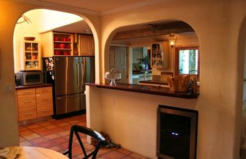 Kitchen and separate breakfast nook view through the arch- wine refrigerator