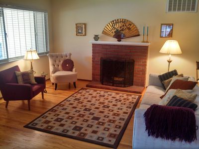 Partial view of living room with cozy wood-burning fireplace.
