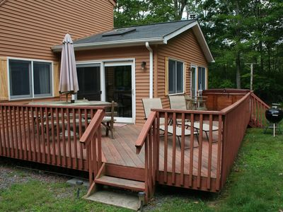 The front wrap-around deck with lounge chairs, picnic table and hot tub.