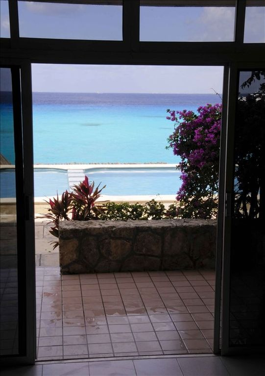 Looking through the sliding glass doors towards the pool and ocean