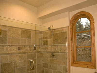 Downstairs bath with large double headed travertine shower