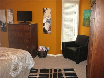 Large guest bedroom with queen bedding, sitting area and local art.