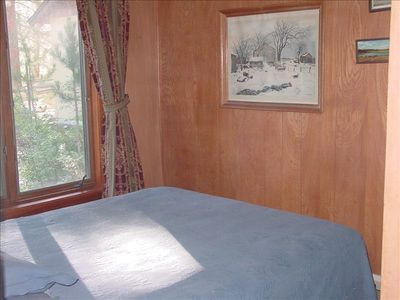 Downstairs bedroom has Queen bed with view of the backyard and meadow