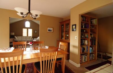 Dining table (partial view) and hall with bookcase