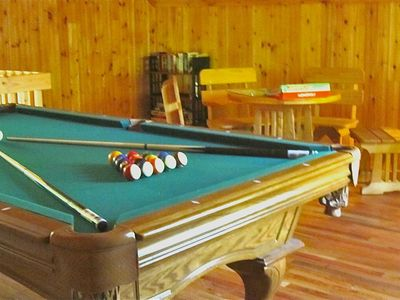 Loft game room with pool table, game table, books, and games.