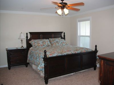 Master bedroom w/king size bed, night stand, adjoining bathroom, and TV