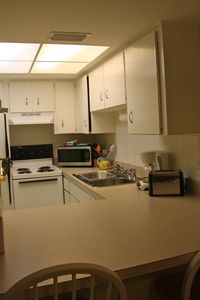 Kitchen, seen through bar area. Fully equipped with dish and cookware.