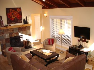Great room with wood-burning fireplace and entertainment center.